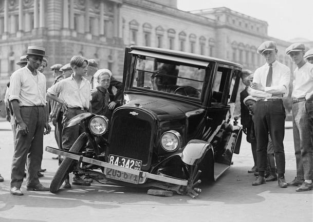 A classic car broken down on a street in 1930s America.